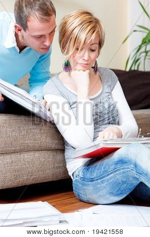 Scenic young family couple at home indoors in living room doing paperwork sitting on couch and floor with lot of paper documents