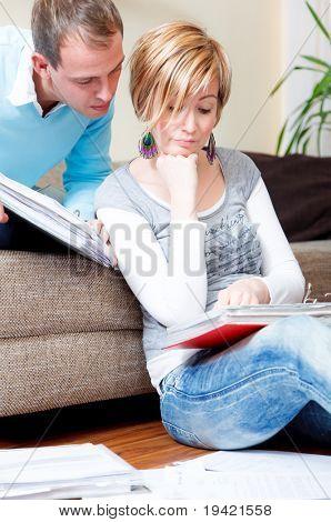 landschaftlich Familie Paares zu Hause drinnen im Wohnzimmer tun schreibarbeit sitzend sofa und Stock