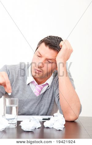 Stressed office man putting aspirin head ache migraine pill in water glass sitting on desk with paper document