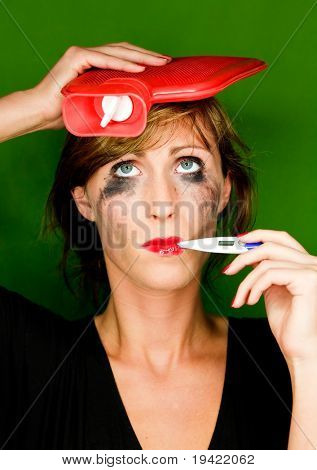 Colorful ill woman with hot-water bag bottle on head measuring temperature having a heavy cold feeling unwell sick