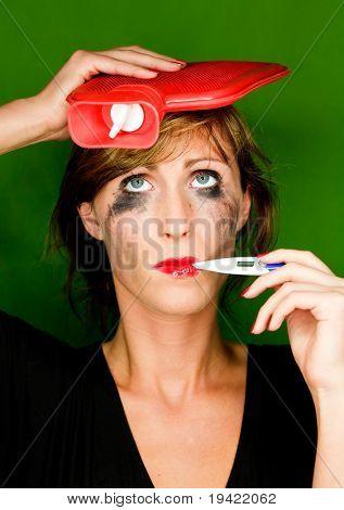 Colorido mujer enferma con botella Bouillotte en cabezas de medida de temperatura con un pesado Behind frío