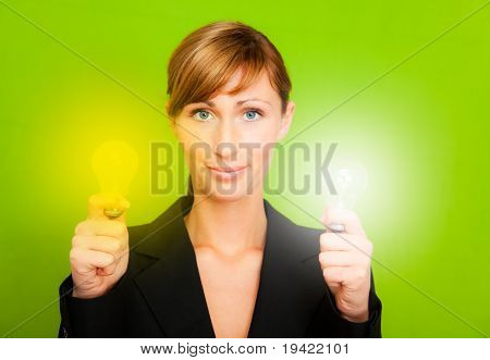Businesswoman holding as professional 2 light bulbs in white and yellow as conceptual symbol of businessperson successful innovation and ecological treatment