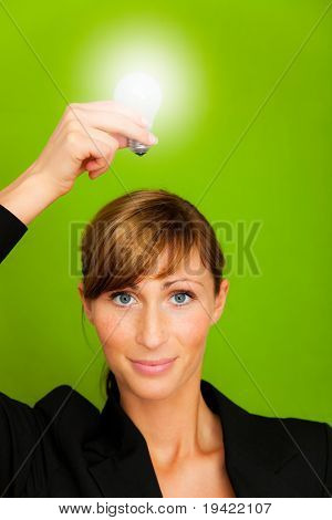 Businesswoman holding as professional 2 lightbulbs in white and yellow as conceptual symbol of businessperson successful innovation and ecological treatment