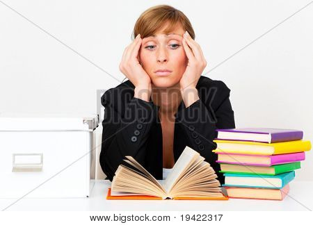 Tired upsed businesswoman on desk while studying a lot of books