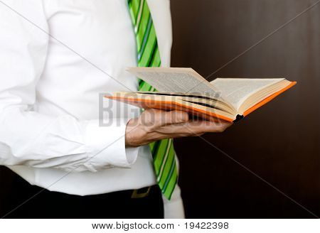 Male business professional reading book of paragraph