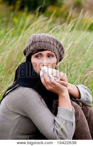 Outdoor sitting relaxing female woman cleaning nose