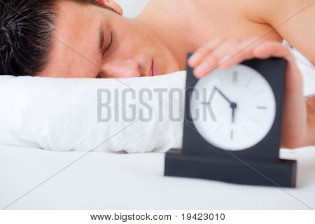 Sleeping man  putting on snooze button while alarm is ringing