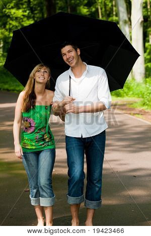 Couple standing or running in park on rainy summer days