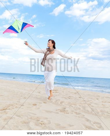 Smiling happy healthy woman walking on beach with kite in autumn spring time