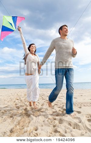 Happy outdoorcouple embracing and running on beach  a kite fly