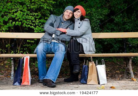 Pair of man and woman couple sitting on bank in park garden after shopping with bags