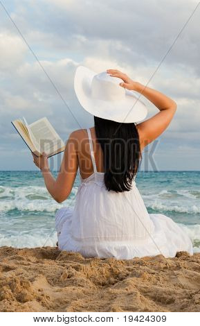Travel woman reads book on the beach