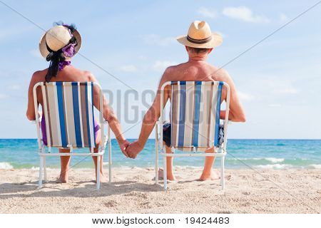 Relaxed summer vacation senior couple of old man and woman sitting on the beach