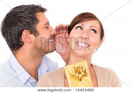 Gift couple holding present whispering ear