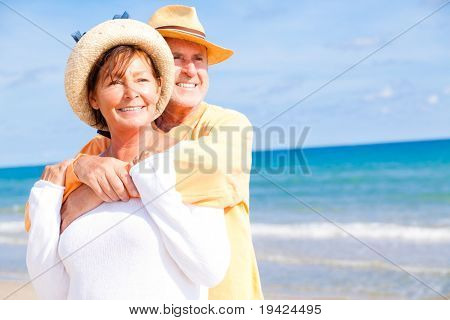 active Relaxed summer vacation senior couple of old man and woman standing on the beach