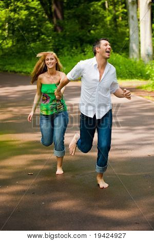 Happy running barefoot couple of two with trees in background smiling walk