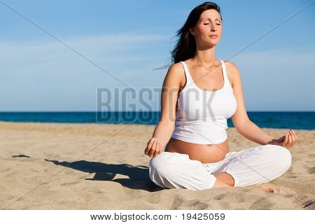 Pregnant female sitting on beach relaxing while vacation holding abdomen being joyful awaiting her newborn baby preparing for childbirth