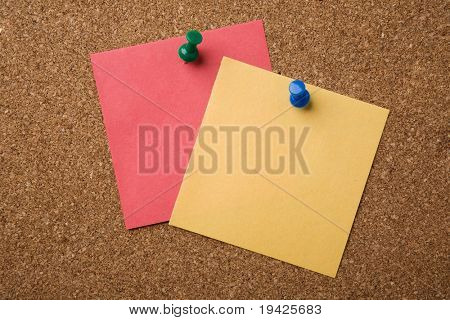 Two notes pinned on a cork board