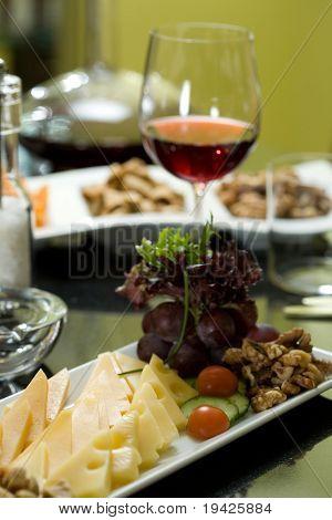 Glass of red wine and assorted cheeses for wine tasting