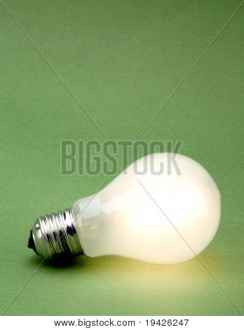 lit lightbulb on a green background