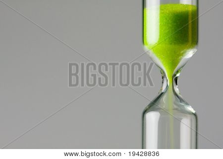 Disminuyendo el verde. Ecología / imagen del concepto de entorno. Arena verde de reloj de arena cayendo.
