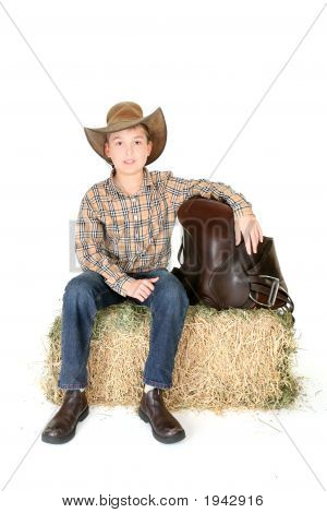 Boy On Hay Bale With Saddle
