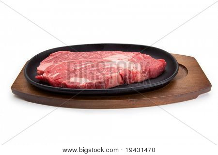 Raw beef steak on a metal grilling plate and wooden tray. Isolated on white with natural shadows.