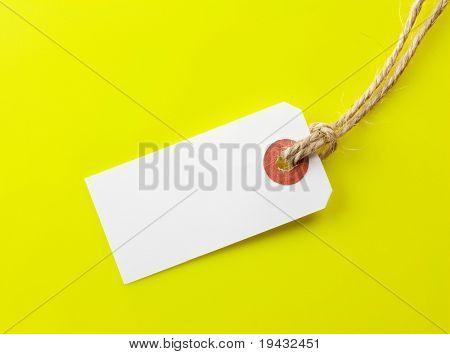 Etiqueta de papel em branco com corda de cânhamo em fundo amarelo.