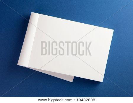 Bloc de notas en blanco con página plegada en superficie azul.