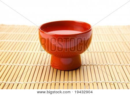 Sake served in a traditional enameled ochoko cup, isolated on white.