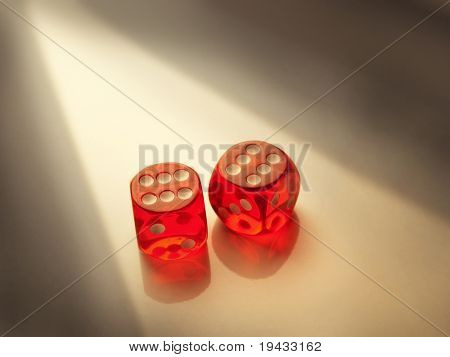 Two red dice, double six under a slit of incandescent light.