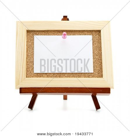 Miniature easel and cork board with blank memo paper, for inserting your message . Isolated on white.