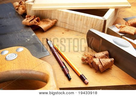 Fine wood working. Saw, hand plane, pencils and a wooden shavings on a work desk under incandescent light.