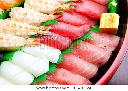 Sushi arranged on a traditional sushi tray, placed on a wooden table top. Isolated on white.