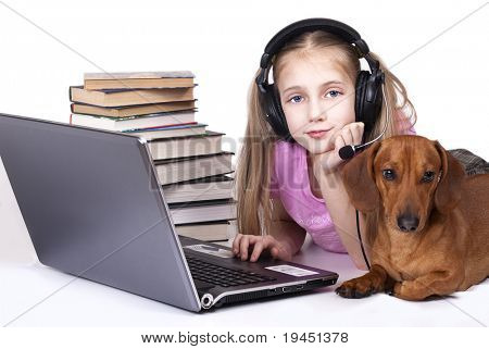 little girl  in Headphones and laptop, dog lies next