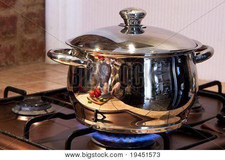 Metal cooking pan on gas burner with burning gas flames