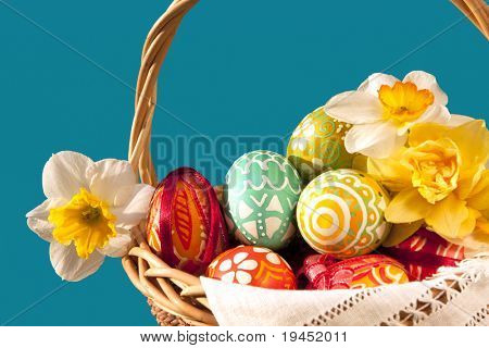 Basket full of Easter eggs and yellow spring daffodils