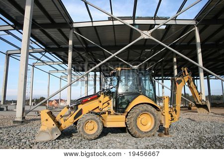 Wheeled tractor on modern storehouse construction site