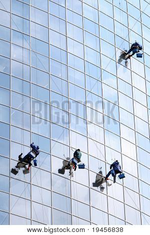 Four workers washing windows in a modern office building