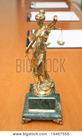 Woman with scales of justice and blank paper on a table