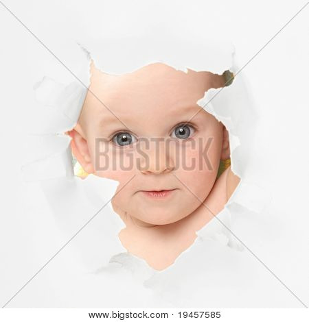 Cute baby looking through paper hole