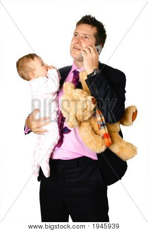 Businessman On The Phone While Holding Baby