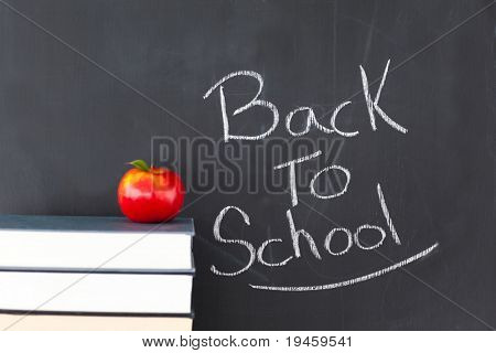 "Stack of books with a red apple and a blackboard with ""back to school"" written on it"