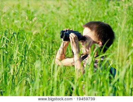 Joven en un campo mirando a través de binoculares