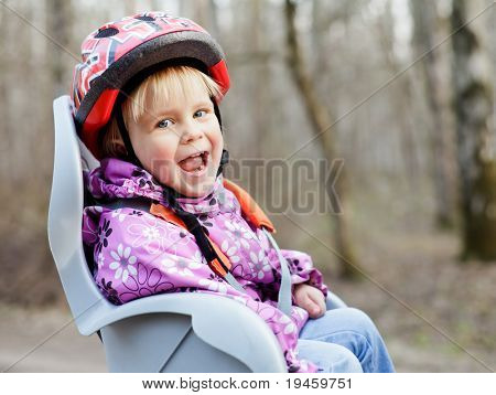 Happy little girl wearing helmet sitting in bycicle child seat