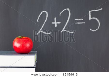 "Stack of books with a red apple and a  blackboard with ""2+2=5"" written on it"