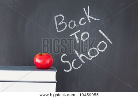 """Stack of books with a red apple and a blackboard with """"back to school"""" written on it"""
