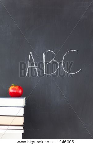 """Stack of books with a red apple and a  blackboard with """"ABC"""" written on it"""