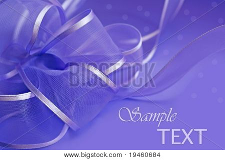 Purple and silver mesh gift bow on matching wrapping paper with copy space.  Macro with extremely shallow dof.