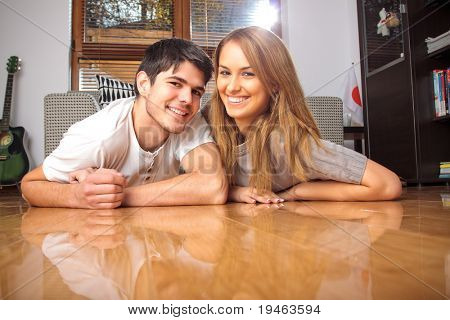 Happy young couple having on the floor